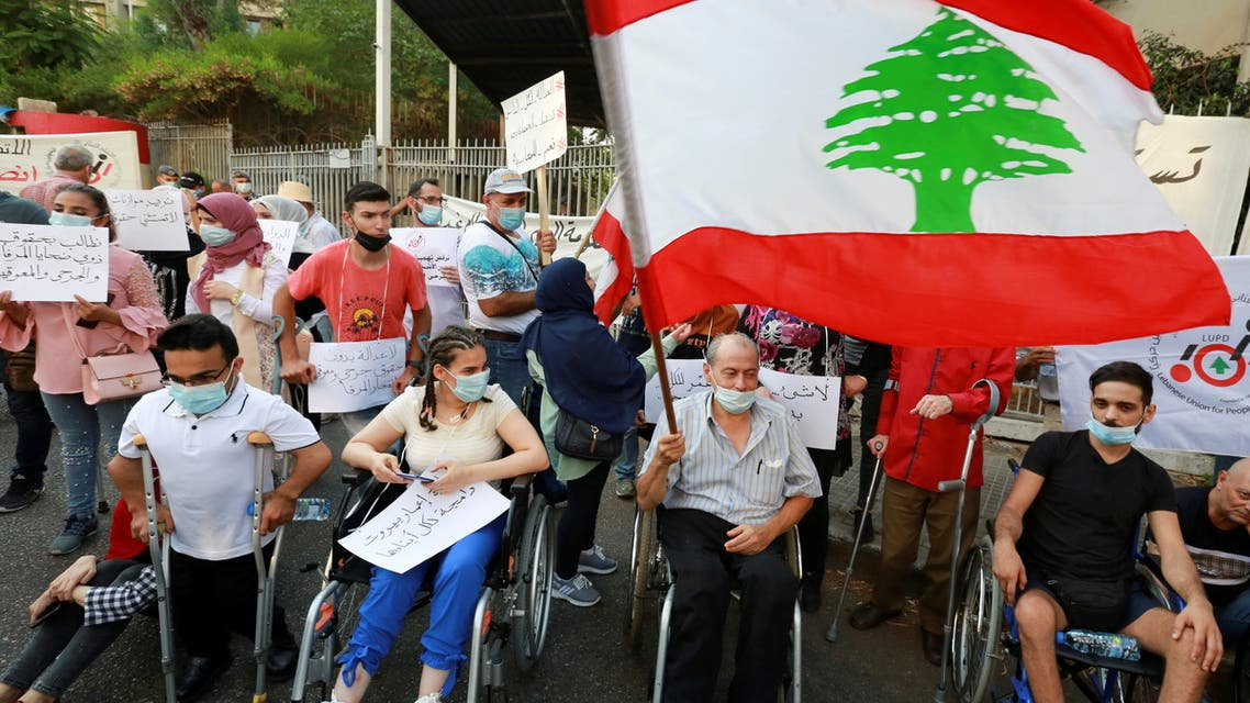 A man holds the Lebanese flag as he sits in a wheelchair during a protest demanding justice for victims of last year's Beirut port blast as Lebanon marks one year anniversary of Beirut port explosion on August 4, outside the Justice Palace in Beirut, Lebanon August 3, 2021. (Reuters)