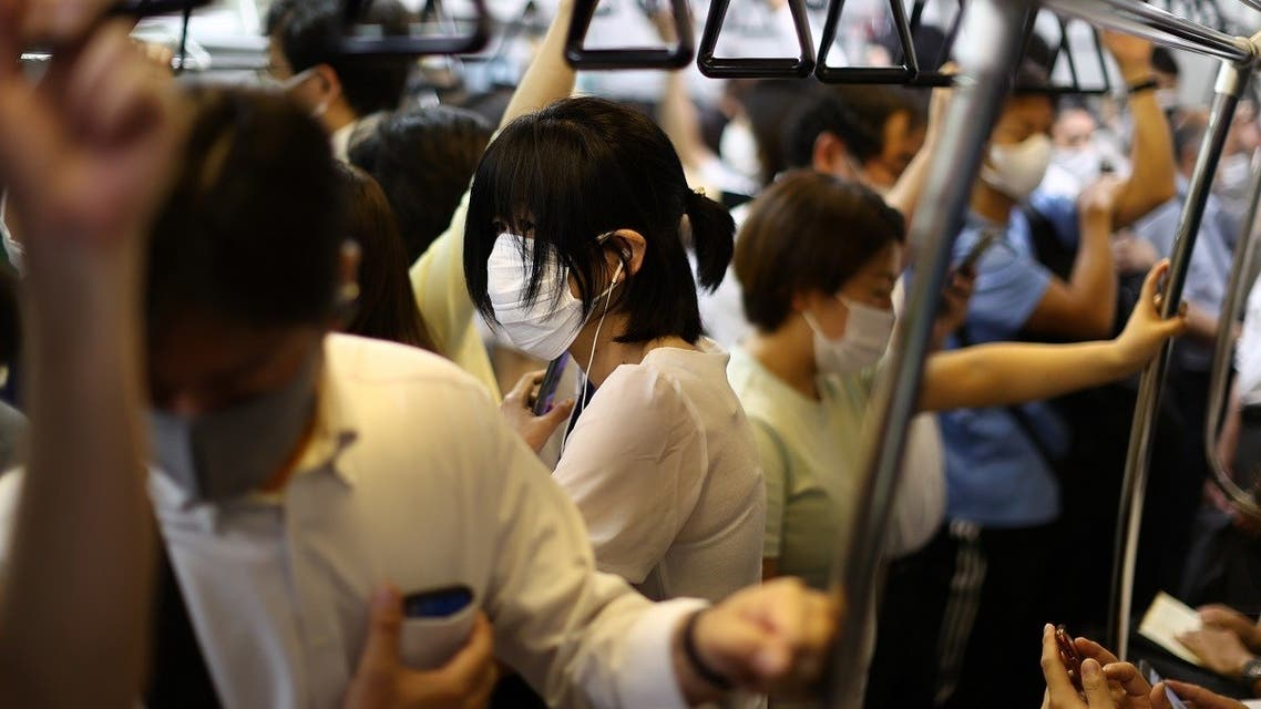 People wearing protective masks amid the coronavirus disease (COVID-19) pandemic take a train on the outskirts of Tokyo, Japan, on August 5, 2021. (Reuters)
