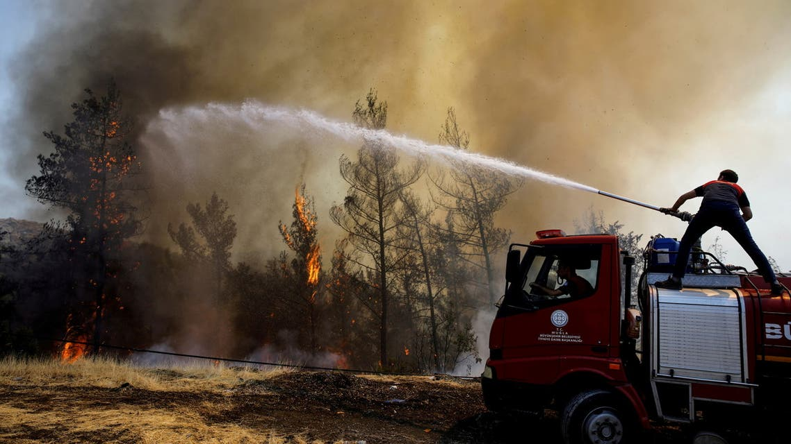 A firefighter tries to extinguish a wildfire near Marmaris, Turkey, August 1, 2021. (Reuters)