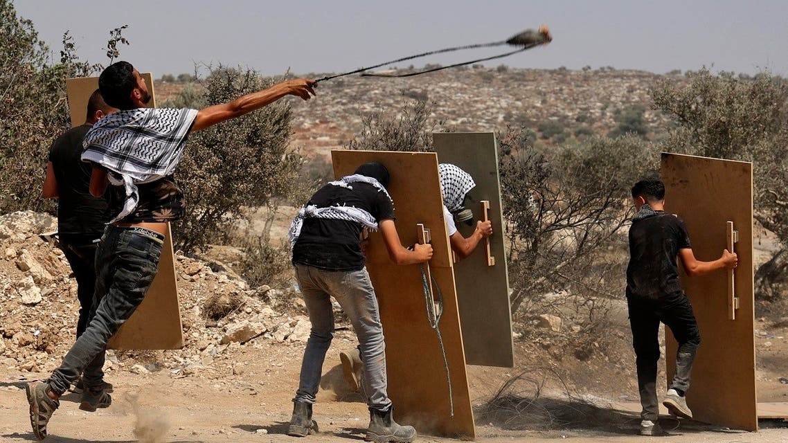 Palestinian protesters use wooden boards as shields amid clashes with Israeli forces during a demonstration against the Israeli outpost of Eviatar in the village of Beita, north of the occupied West Bank, on August 6, 2021. (Reuters)