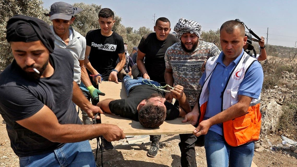 Palestinian protesters and medics evacuate an injured youth amid clashes with Israeli forces during a demonstration against the Israeli outpost of Eviatar in the village of Beita, north of the occupied West Bank, on August 6, 2021. (AFP)
