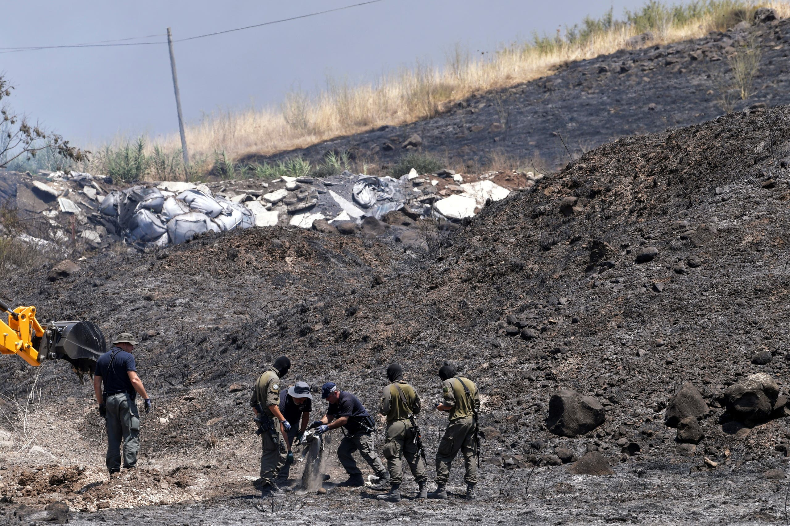 An Israeli bombs expert, accompanied by two soldiers, inspects the remains of a rocket that was fired at Israel from Lebanon, in Kiryat Shmona, Israel August 4, 2021. (Reuters)