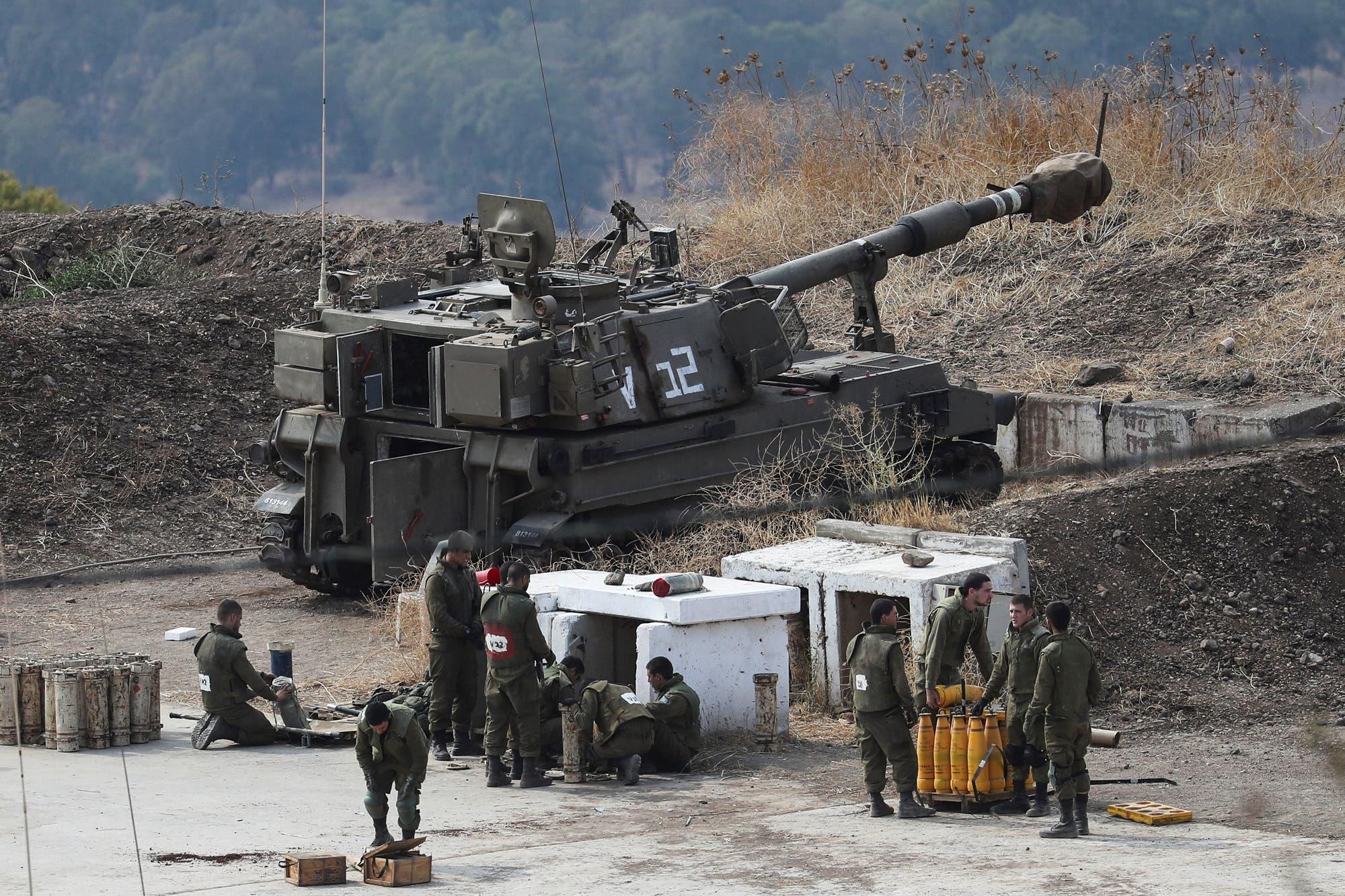 جنود إسرائيليون يقفون على الجانب الإسرائيلي من الحدود مع لبنان (رويترز)