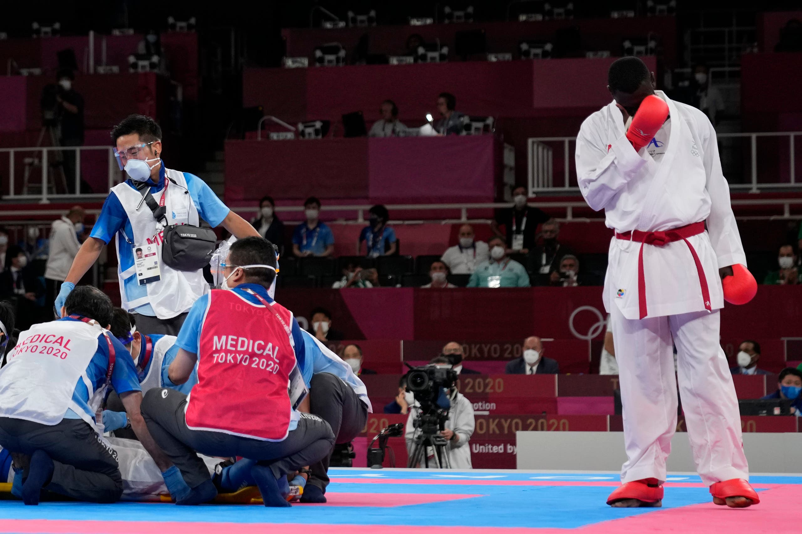 Tarek Hamedi of Saudi Arabia, right, reacts as medical personnel attend to Sajad Ganjzadeh of Iran after he was injured in their men's kumite +75kg gold medal bout for karate at the 2020 Summer Olympics, Saturday, Aug. 7, 2021, in Tokyo, Japan. (AP)