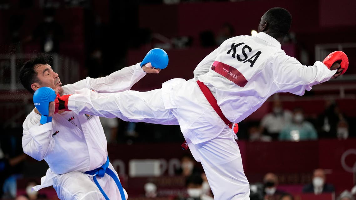 Sajad Ganjzadeh of Iran, left, is injured while competing against Tareg Hamedi of Saudi Arabia in their men's kumite +75kg gold medal bout for karate at the 2020 Summer Olympics, Saturday, Aug. 7, 2021, in Tokyo, Japan. (AP)