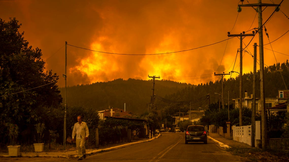 A local resident walks as a wildfire rages near the village of Gouves, on Euboea island, second largest Greek island, on August 8, 2021. Hundreds of firefighters battled a blaze on the outskirts of Athens as several fires raged in Greece.