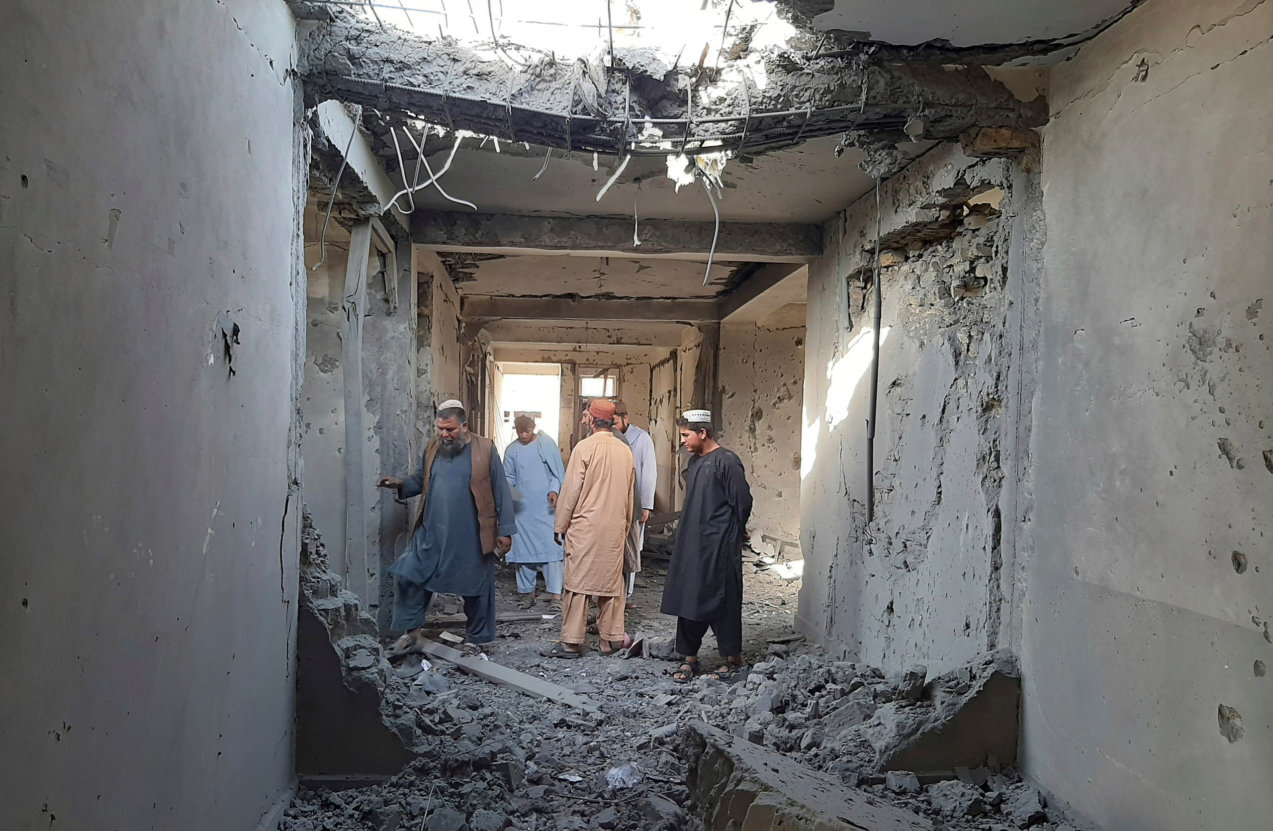 Afghans inspect a damaged clinic after airstrikes in Lashkar Gah city of Helmand province, southern of Kabul, Afghanistan, Sunday, Aug. 8, 2021. Airstrikes in southern Afghanistan damaged a health care clinic and high school in the capital of Helmand province, a provincial council member said Sunday. (AP)