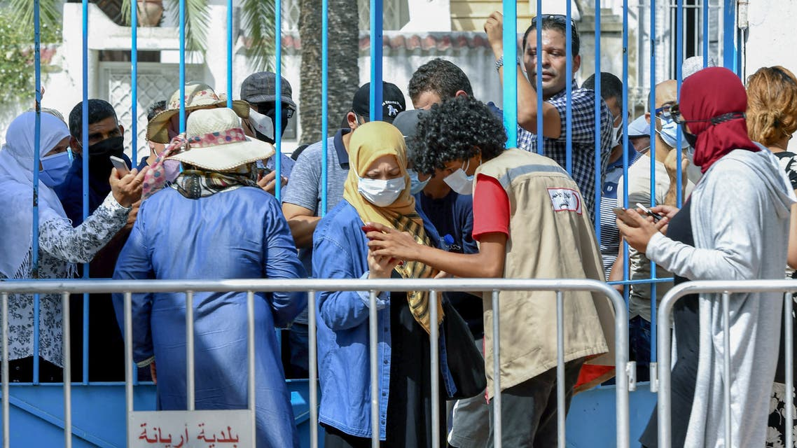 Tunisians wait for their turn to receive a COVID-19 vaccine at an inoculation center in Ariana governorate near the capital Tunis on August 8, 2021. (AFP)