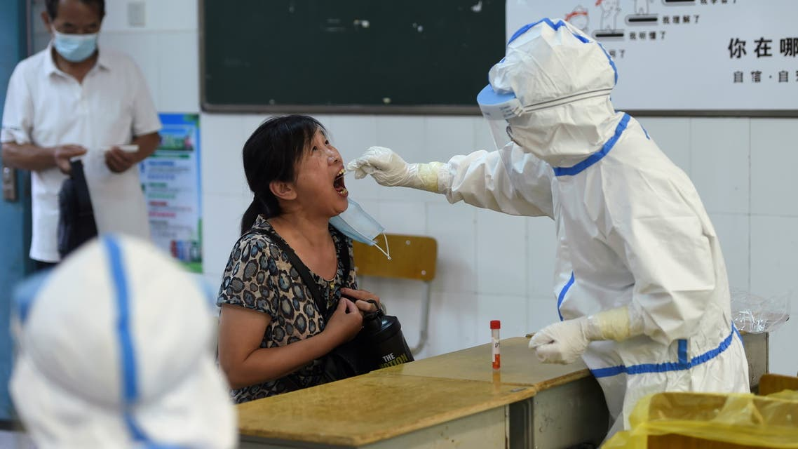 A medical worker in a protective suit collects a swab from a resident during a citywide nucleic acid testing following new cases of the coronavirus disease (COVID-19) in Wuhan, Hubei province, China, August 3, 2021. Picture taken August 3, 2021. REUTERS/Stringer CHINA OUT.