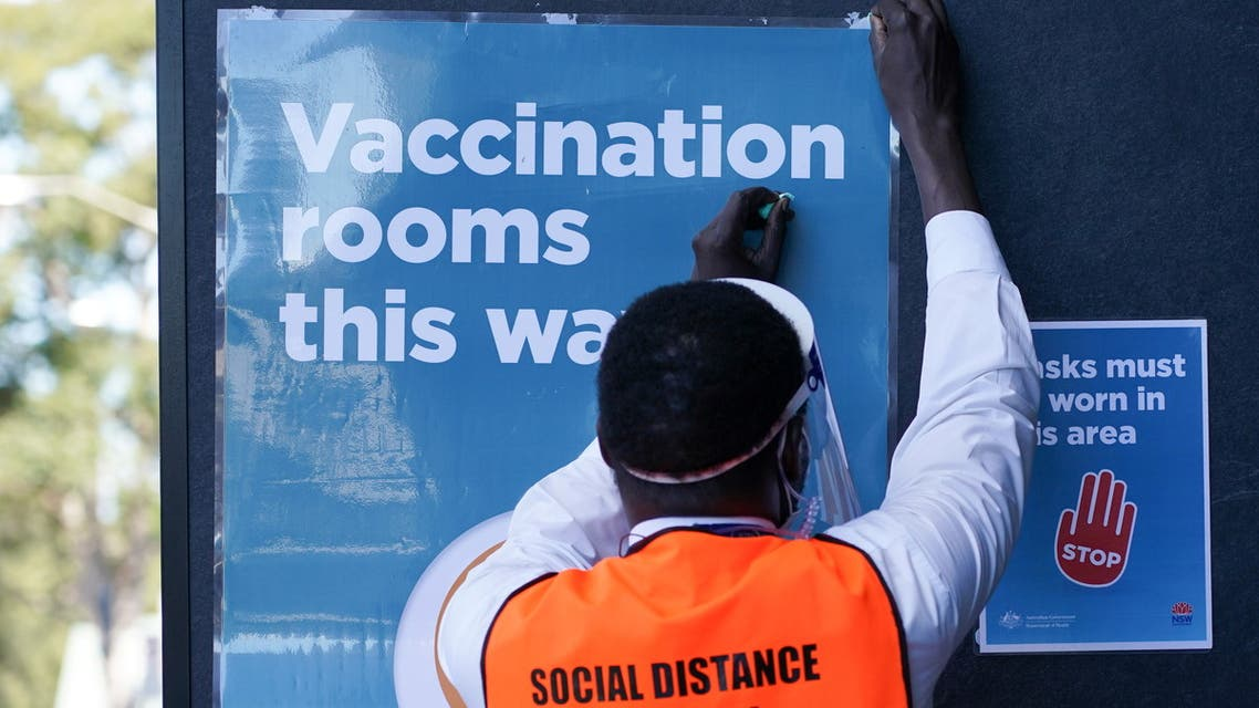 A staff member straightens a sign outside a coronavirus disease (COVID-19) vaccination clinic at the Bankstown Sports Club as the city experiences an extended lockdown, in Sydney, Australia, August 3, 2021. (Reuters)