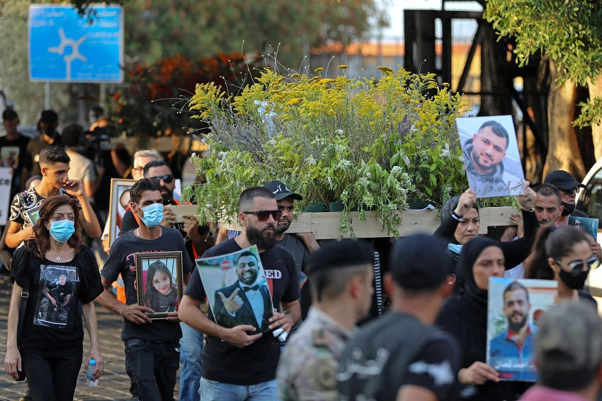 Families of the August 4 victims joined by protestors march with imitation coffins and portraits of their loved ones during a symbolic funeral procession from Beirut port on August 8, 2021, days after the first anniversary of a vast dockside explosion that left more than 200 people dead. (AFP)
