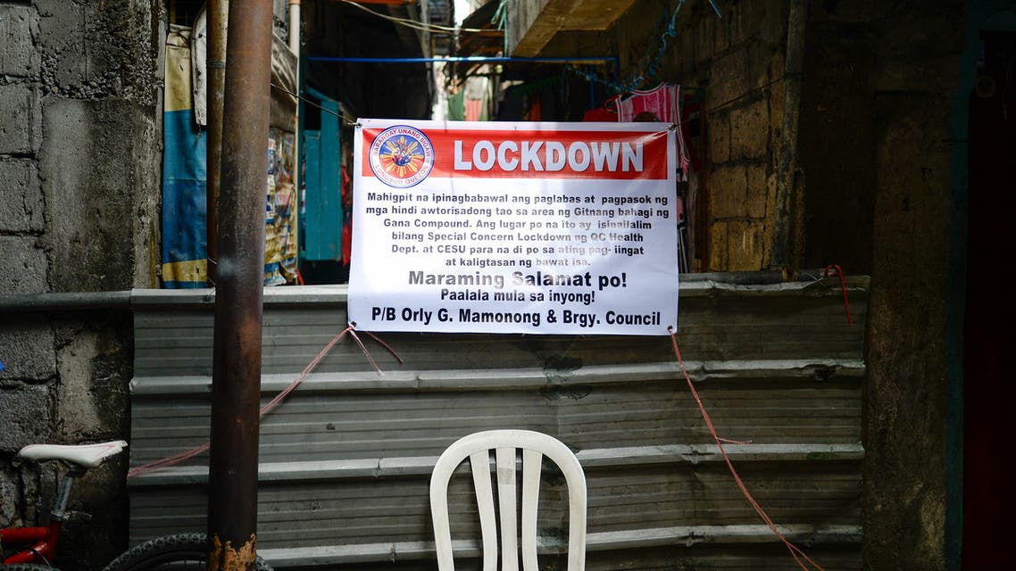 A makeshift barrier and a sign indicating that the street is under lockdown are seen, amid rising coronavirus disease (COVID-19) cases, in Quezon City, Metro Manila, Philippines, April 20, 2021. (Reuters)
