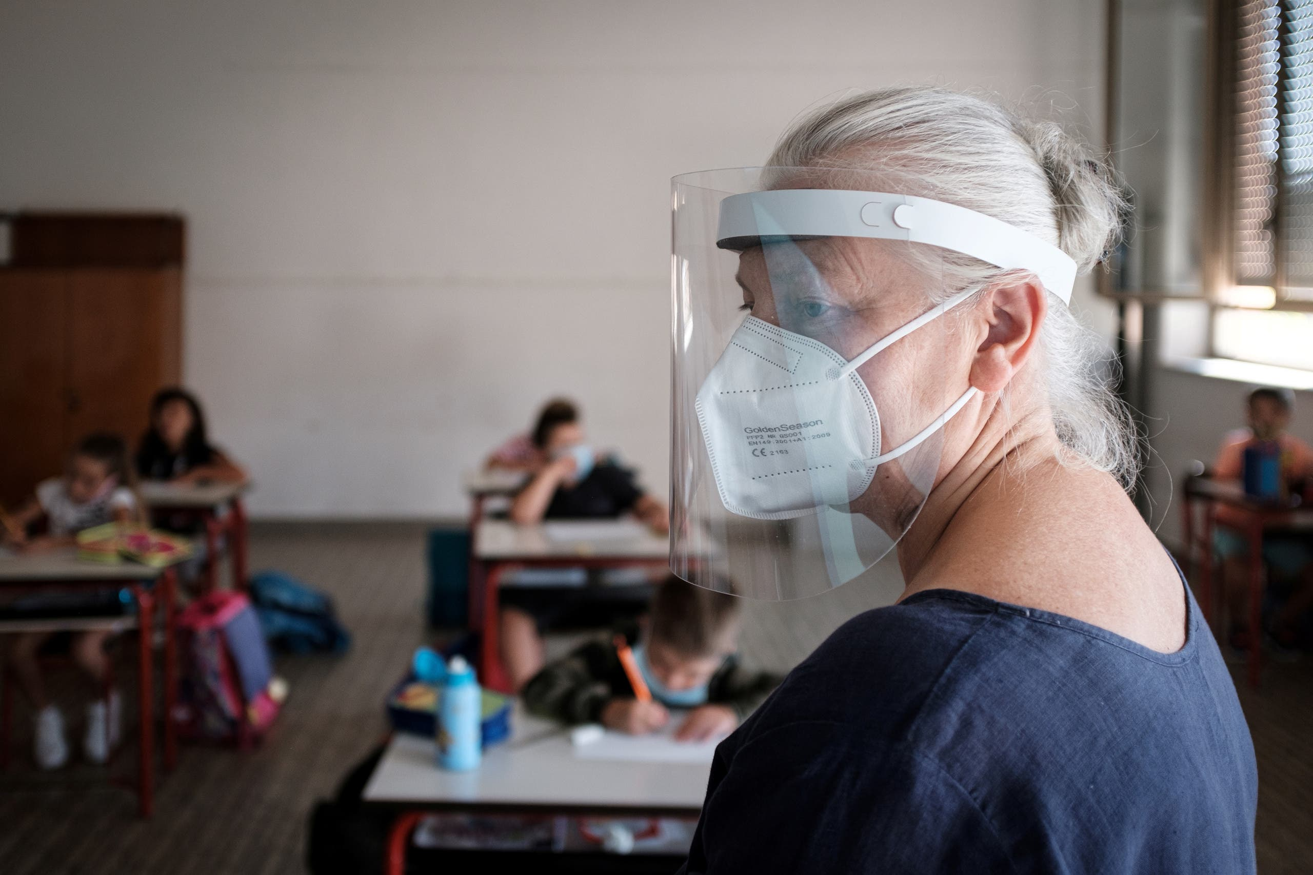 Teacher Marzio Toniolo took this photo of a staff member at his primary school wearing a mask and protective shield during a lesson, as children returned for the first time since the end of February when Italy's original 'red zone' towns were put under lockdown, adhering to strict regulations to avoid coronavirus disease (COVID-19) contagion, in Santo Stefano Lodigiano, Italy, September 14, 2020. Picture taken September 14, 2020. (Reuters)