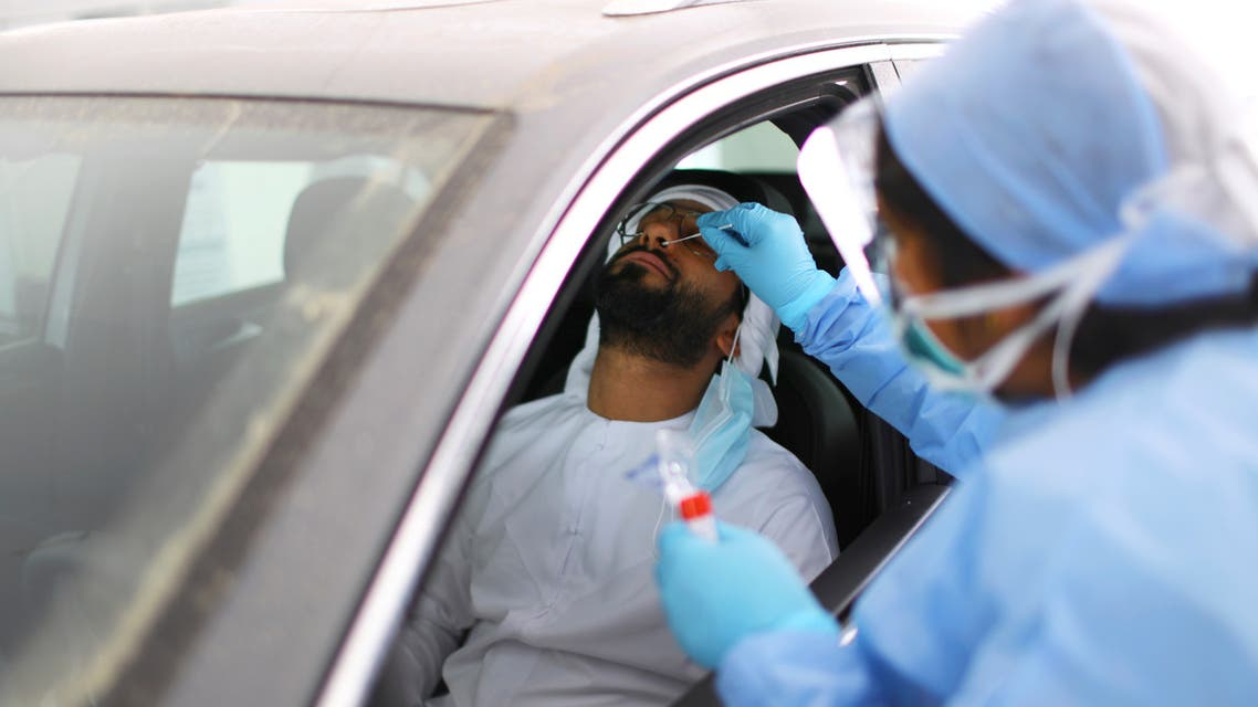 A member of medical staff wearing a protective face mask and gloves takes a swab from a man during drive-thru coronavirus disease testing (COVID-19) at a screening centre in Abu Dhabi, United Arab Emirates March 30, 2020. (File photo: Reuters)