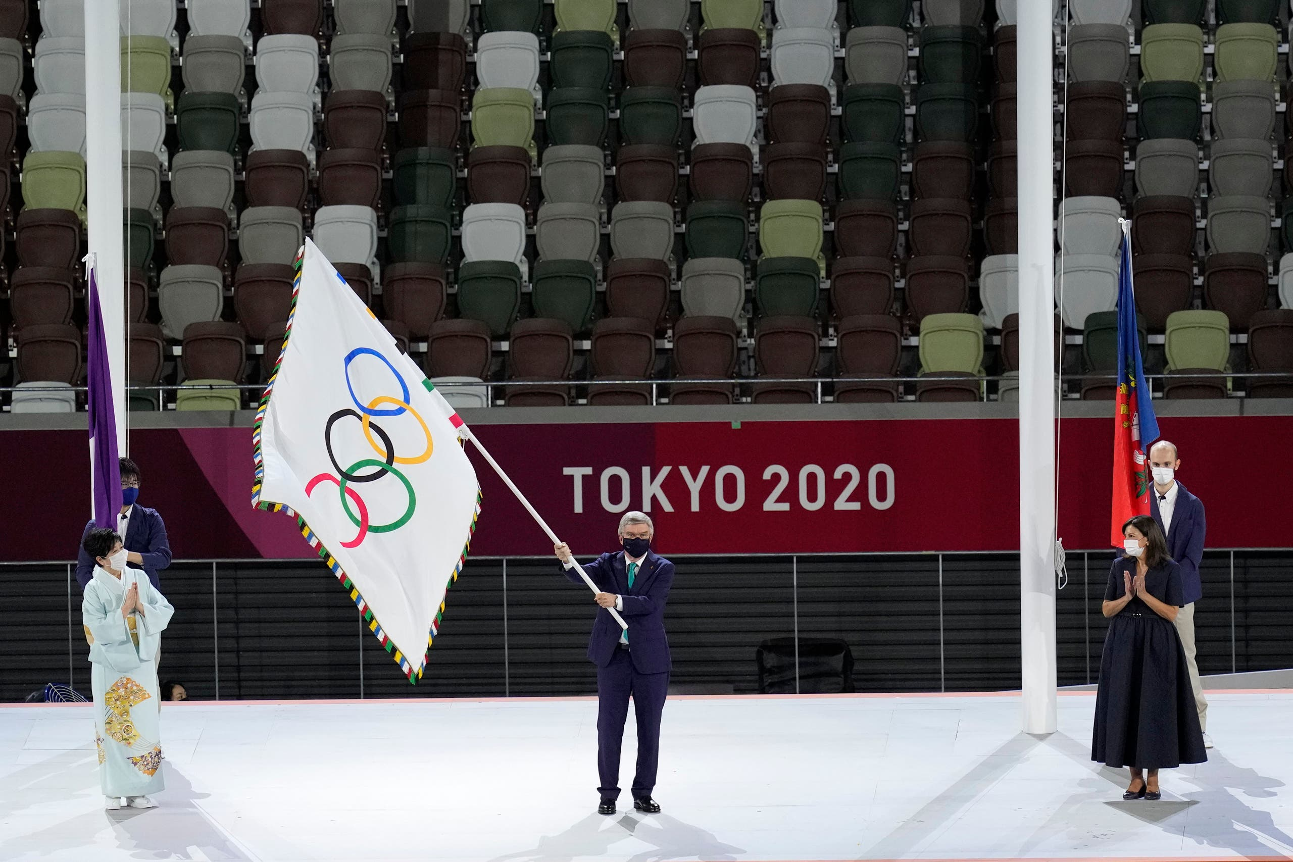 International Olympic Committee's President Thomas Bach waves the Olympic flag as Tokyo Gov. Yuriko Koike, left, and Paris mayor Anne Hidalgo, right, watch during the closing ceremony in the Olympic Stadium at the 2020 Summer Olympics, Sunday, Aug. 8, 2021, in Tokyo, Japan. (AP)