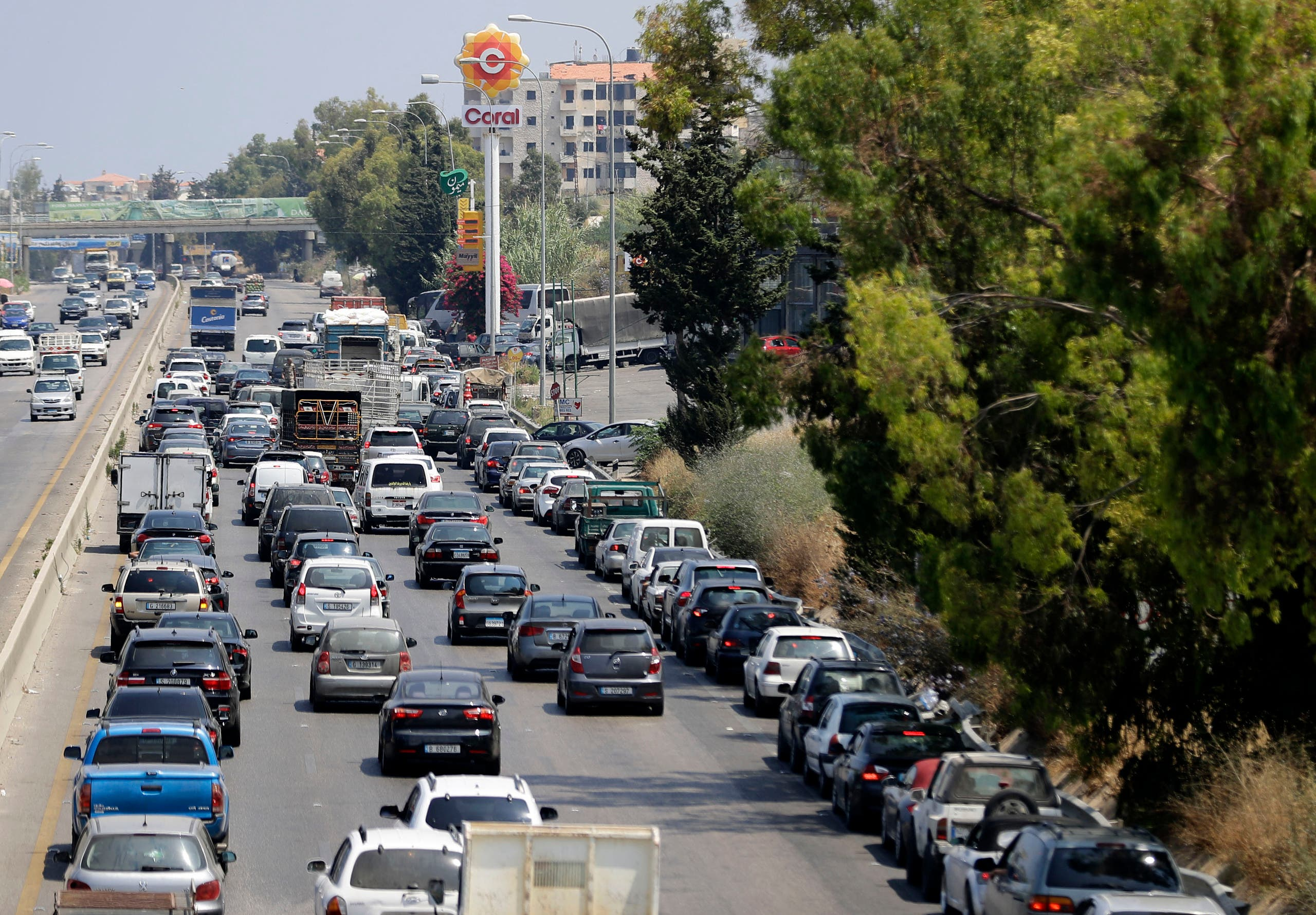 Vehicles on the right lane adjacent to the petrol station queue-up for fuel as traffic flows through the area of Naameh on the Beirut-Sidon highway, south of the Lebanese captial, on June 24, 2021 amidst severe fuel shortages. (File photo: AFP)