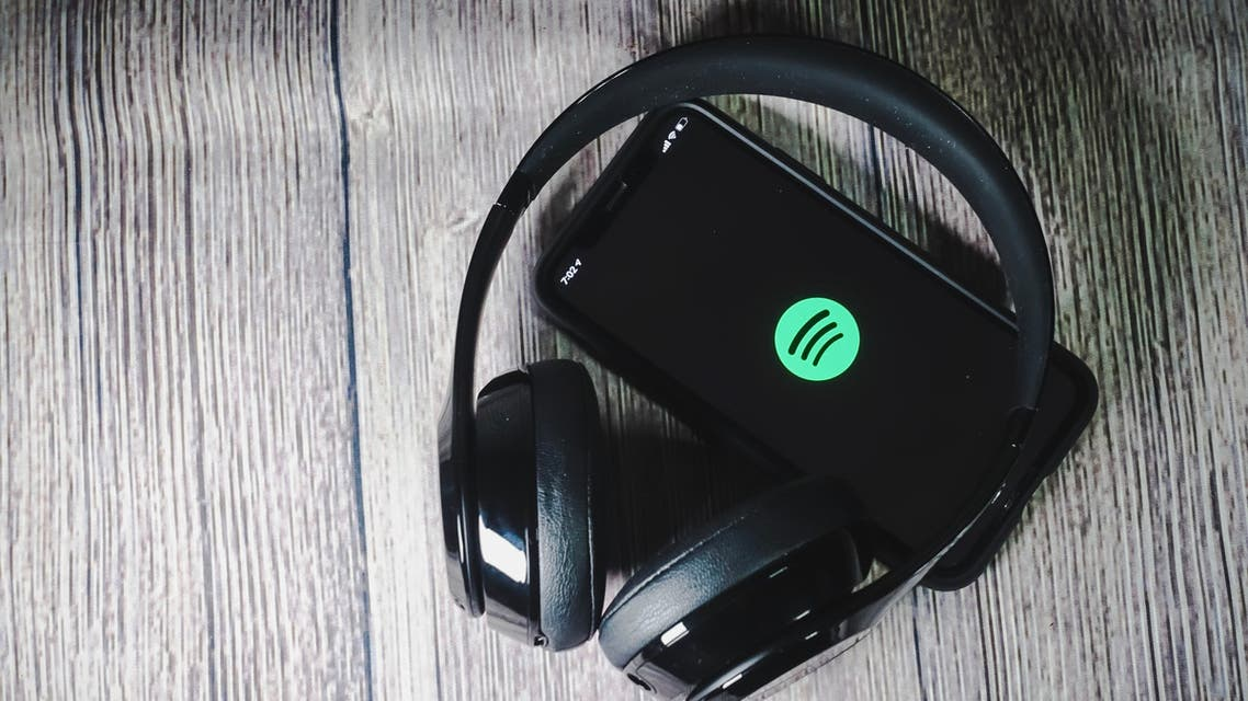 An iphone 11 screen showing spotify icon with beats earphone, perfect for listening musics on the go