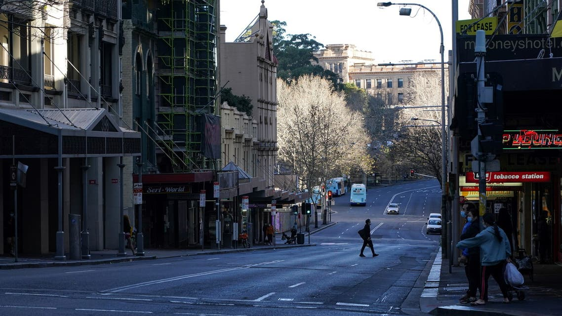 A pedestrian crosses an almost empty street in the City Centre during a lockdown to curb the spread of the coronavirus disease (COVID-19) outbreak in Sydney, Australia, July 21, 2021. (Reuters)