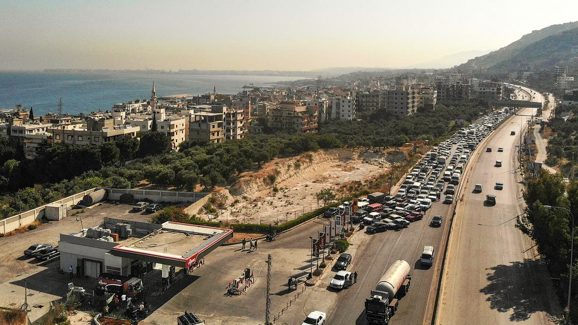 An aerial view show vehicles on the left lane adjacent to a petrol station queueing-up for fuel as traffic flows through on the Tripoli-Beirut highway at the coastal city of Qalamun in northern Lebanon on July 1, 2021 amidst severe fuel shortages.