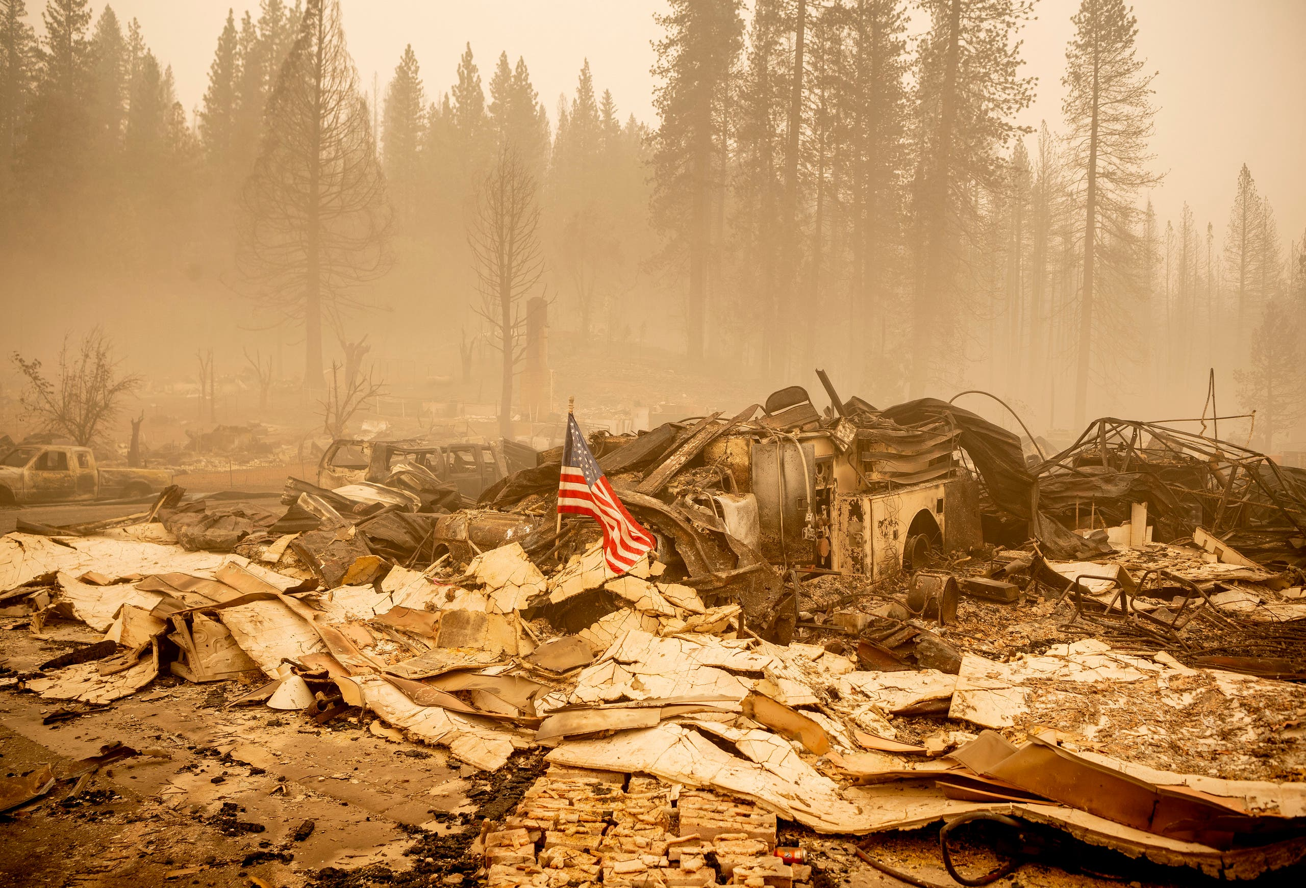 An American flag is placed on a burned fire engine at a burned fire station in downtown Greenville, California on August 7, 2021. (AFP)