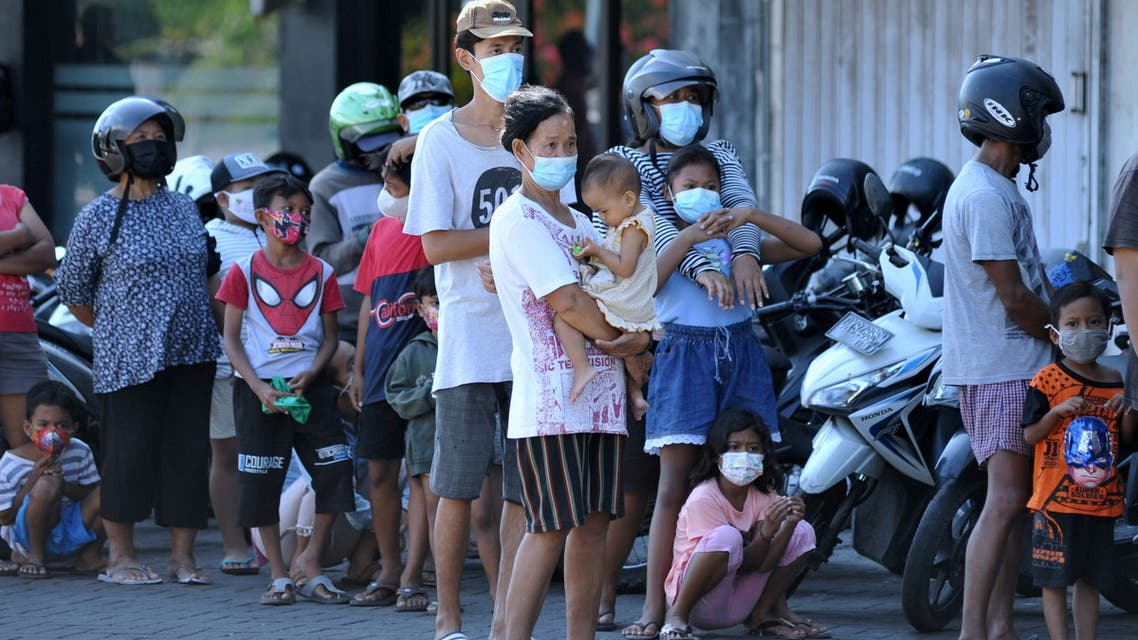 People wearing protective masks stand in line to receive a free meal amid a surge of coronavirus disease (COVID-19) cases in Bali, Indonesia July 28, 2021. (Reuters)
