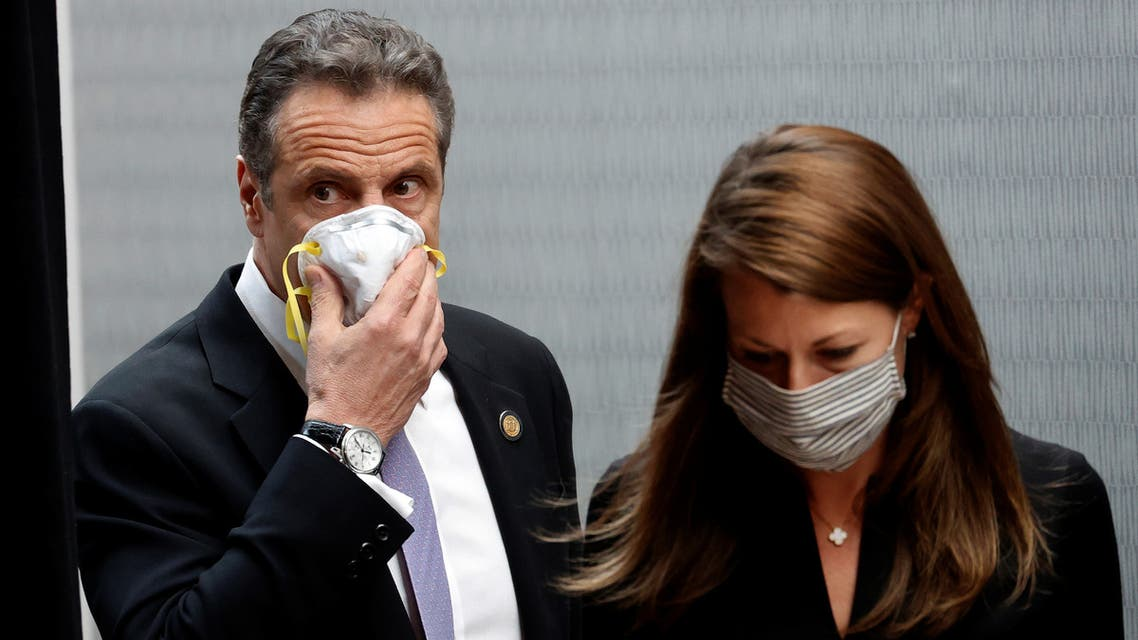 New York Governor Andrew Cuomo holds a protective mask to his face as he and Secretary to the Governor Melissa DeRosa arrive for a daily briefing at New York Medical College during the outbreak of the coronavirus disease (COVID-19) in Valhalla, New York, U.S., May 7, 2020. REUTERS/Mike Segar