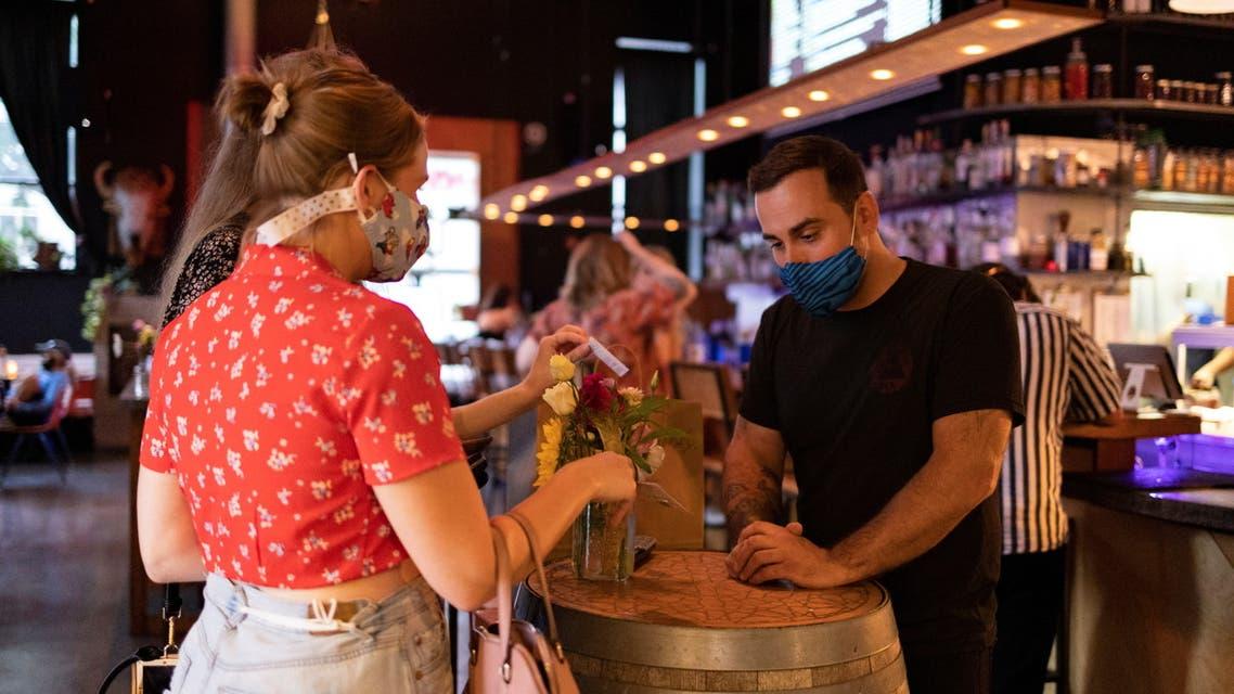 Customers show proof of their coronavirus disease (COVID-19) vaccinations before entering the restaurant Martha, in Philadelphia, Pennsylvania, US, August 7, 2021. (Reuters)