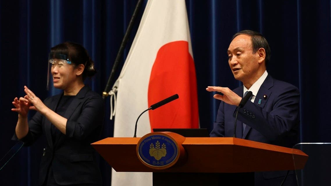 Japan's Prime Minister Yoshihide Suga (R) attends a news conference on Japan's response to the coronavirus pandemic during the Tokyo 2020 Olympic Games in Tokyo, Japan. (AP)