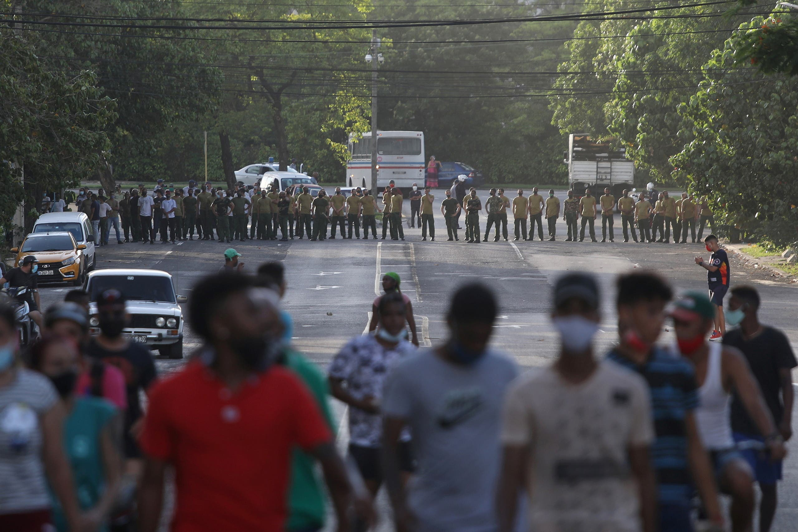 Demonstrators walk away from army soldiers blocking a road during a protest against and in support of the government, amidst the coronavirus disease (COVID-19) outbreak, in Havana, Cuba July 11, 2021. (Reuters)