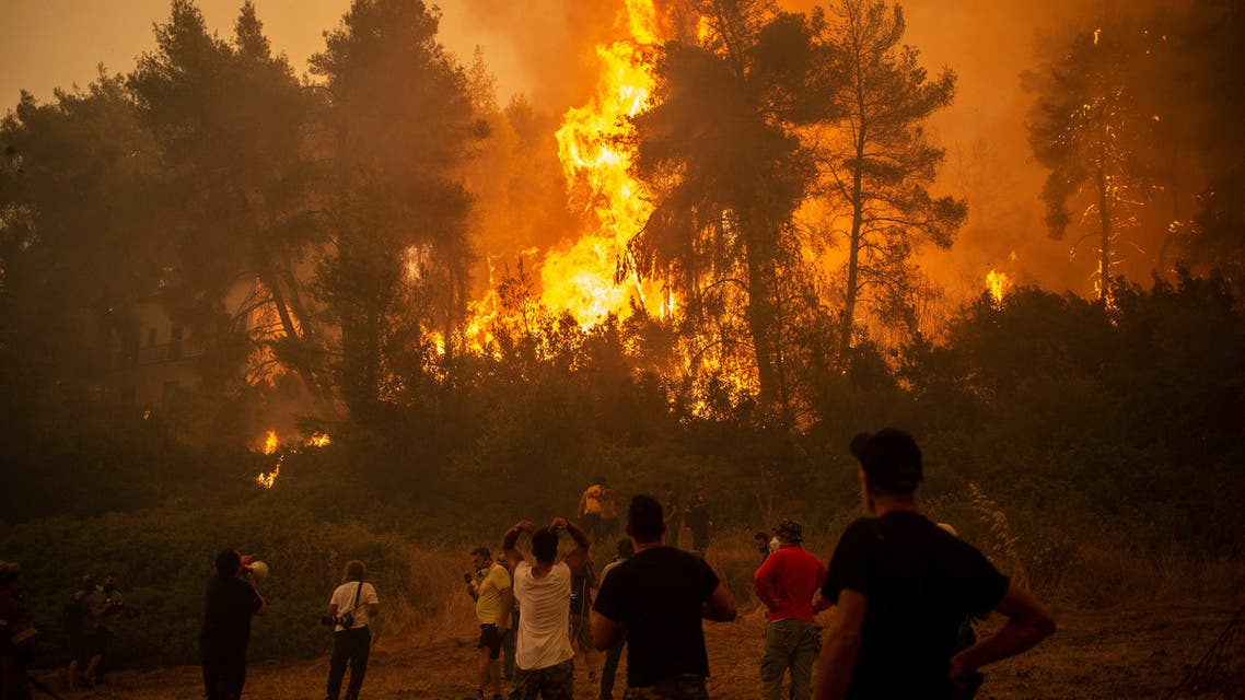 A local uses a megaphone as others observe a large forest fire approaching the village of Pefki on Evia (Euboea) island, Greece's second largest island, on August 8, 2021. (AFP)