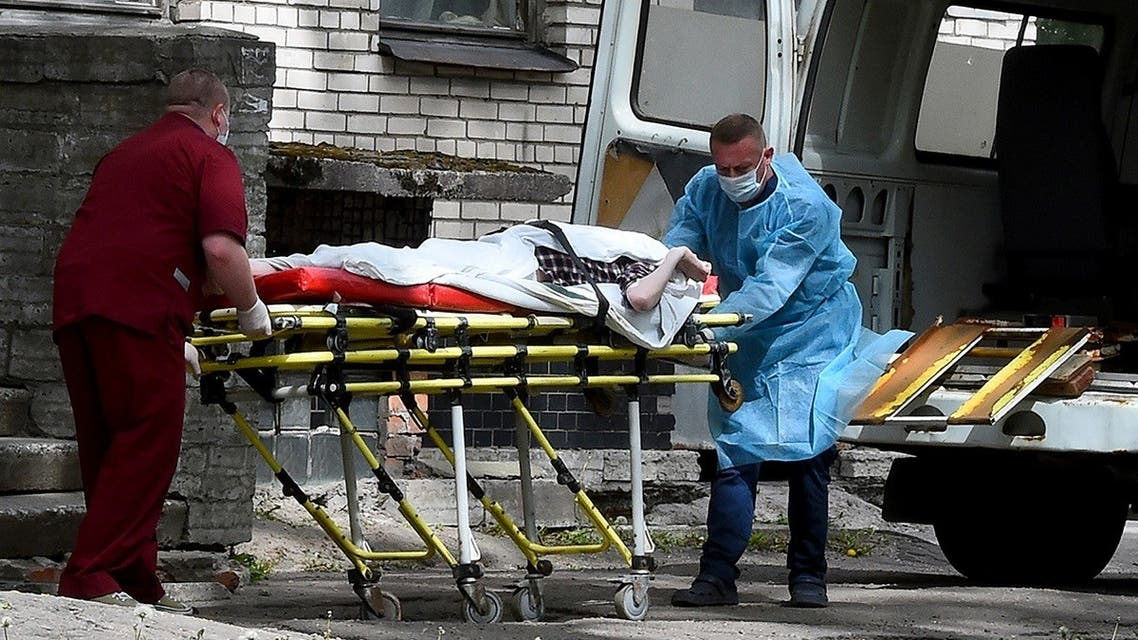 A file photo shows two nurses carry a patient at the Botkin hospital for infectious diseases, Saint Petersburg's main coronavirus treatment center, June 3, 2020. (Olga Maltseva/AFP)