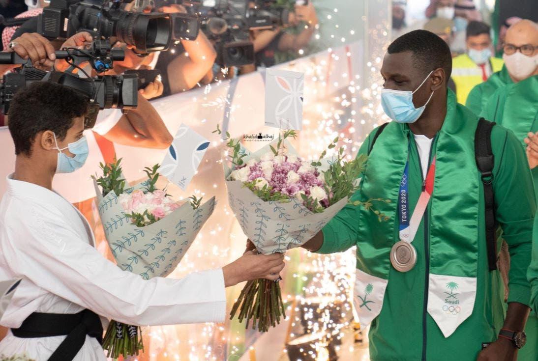 Saudi Arabian Olympic champion and Karate player Tarek Hamedi accepts a bouquet of flowers from an aspiring karate player. (Twitter)