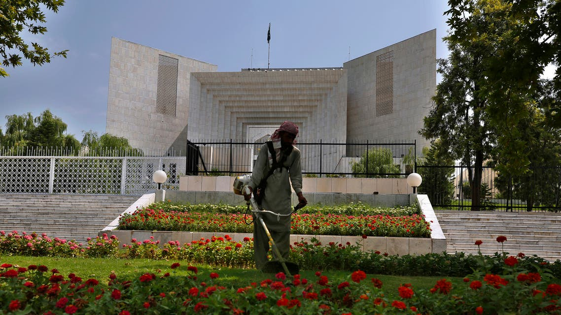 A worker mows the front lawn of the Supreme Court building where the hearing of the Hindu temple attack case is held in Islamabad, Pakistan, Friday, Aug. 6, 2021. (AP)