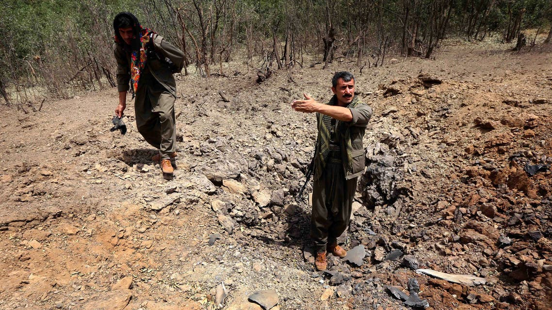 Members of the Kurdistan Workers' Party (PKK) inspect a crater reportedly caused by an air strikes by Turkish warplanes on July 29, 2015 in the Qandil mountain, the PKK headquarters in northern Iraq. The leadership of Iraqi Kurdistan on July 25, 2015 condemned Turkish air strikes against positions of PKK Kurdish rebels in its autonomous region in the north of Iraq. AFP PHOTO / SAFIN HAMED