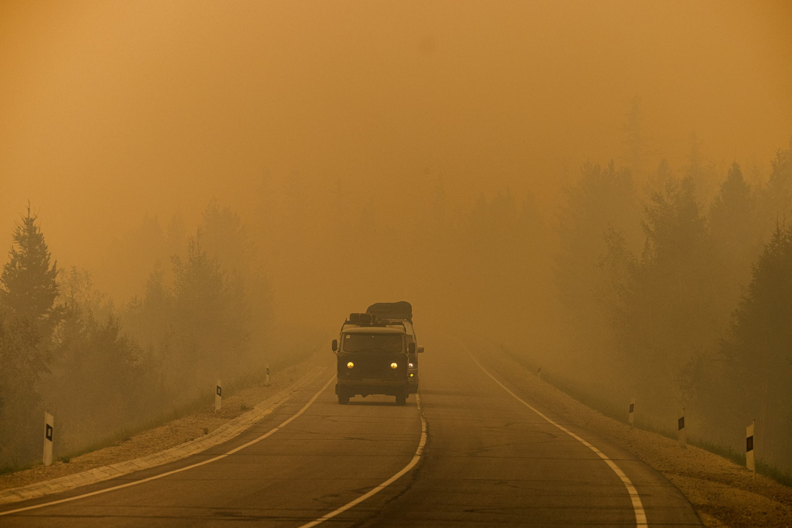 Cars drive down a road covered with smoke from nearby forest fires between the village of Magaras and the city of Yakutsk, in the republic of Sakha, Siberia, on July 27, 2021. (AFP)