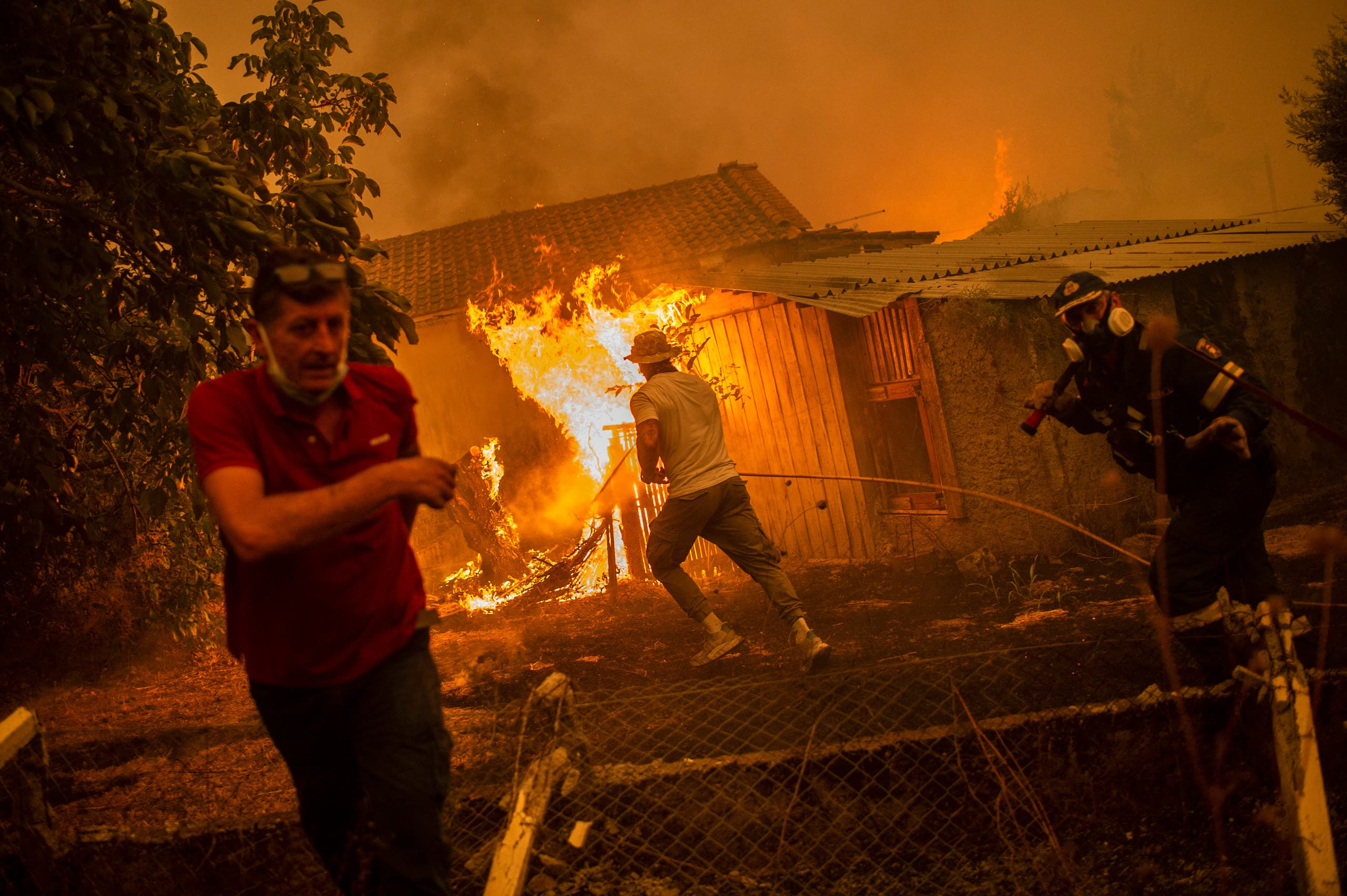 A firefighter and locals rush to a burning house in an attempt to extinguish forest fires that are approaching the village of Pefki on Evia (Euboea) island, Greece's second largest island, on August 8, 2021. (AFP)