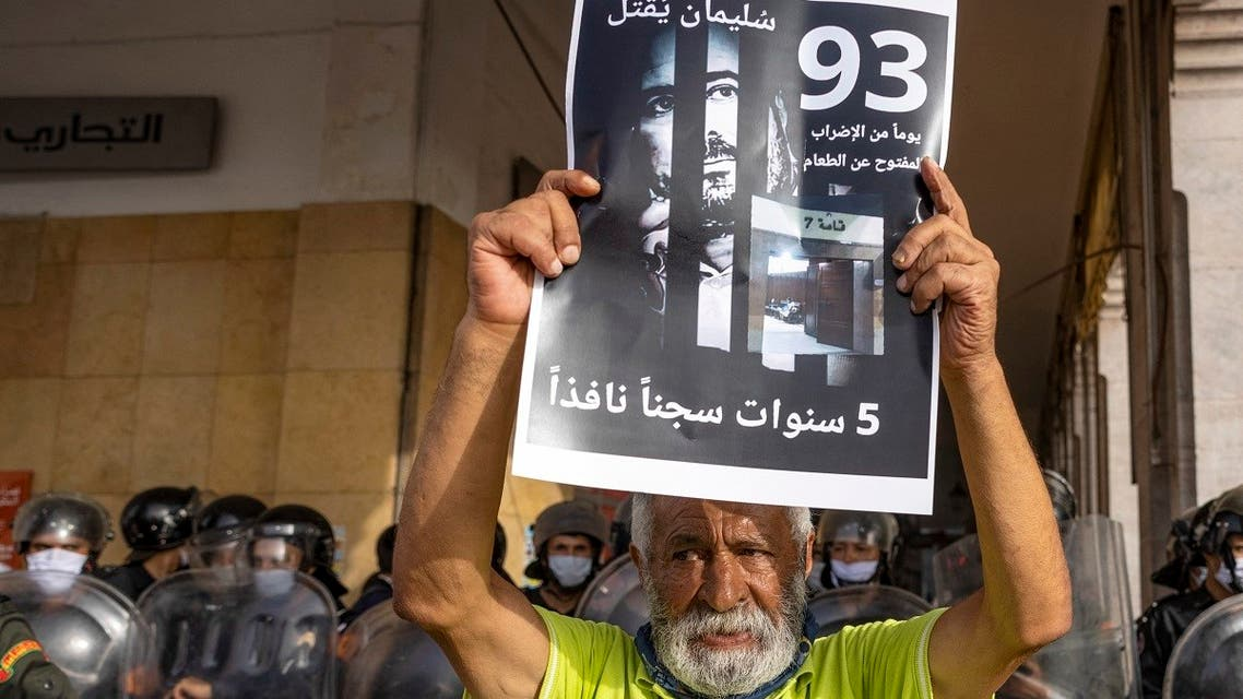 A Moroccan activist holds a banner with the image of Moroccan journalist Soulaimane Raissouni, who was sentenced to five years in prison for sexual assault, as his supportes protest on July 10, 2021, in the capital Rabat demanding his release.  (AFP)