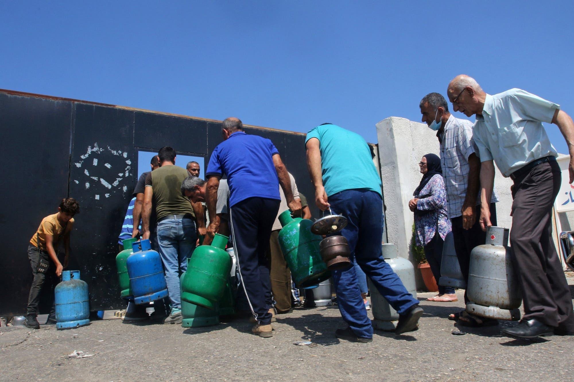 لبنانيون ينتظرون ملء قوارير الغاز في صيدا يوم 10 أغسطس (فرانس برس)