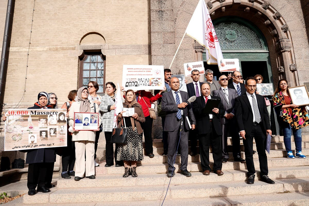 Supporters of People's Mojahedin Organization of Iran protest outside Stockholm District Court on the first day of the trial of Hamid Noury, 60, accused of involvement in the massacre of political prisoners in Iran in 1988, Stockholm, Sweden, on August 10, 2021. (Reuters)