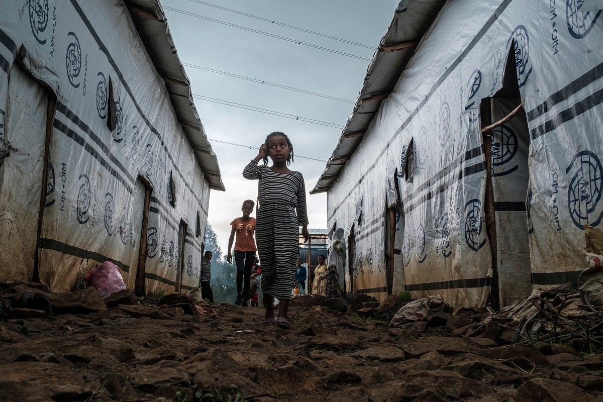 Internally displaced children run in an alley of a camp in the town of Azezo, Ethiopia, on July 12, 2021. (Eduardo Soteras/AFP)