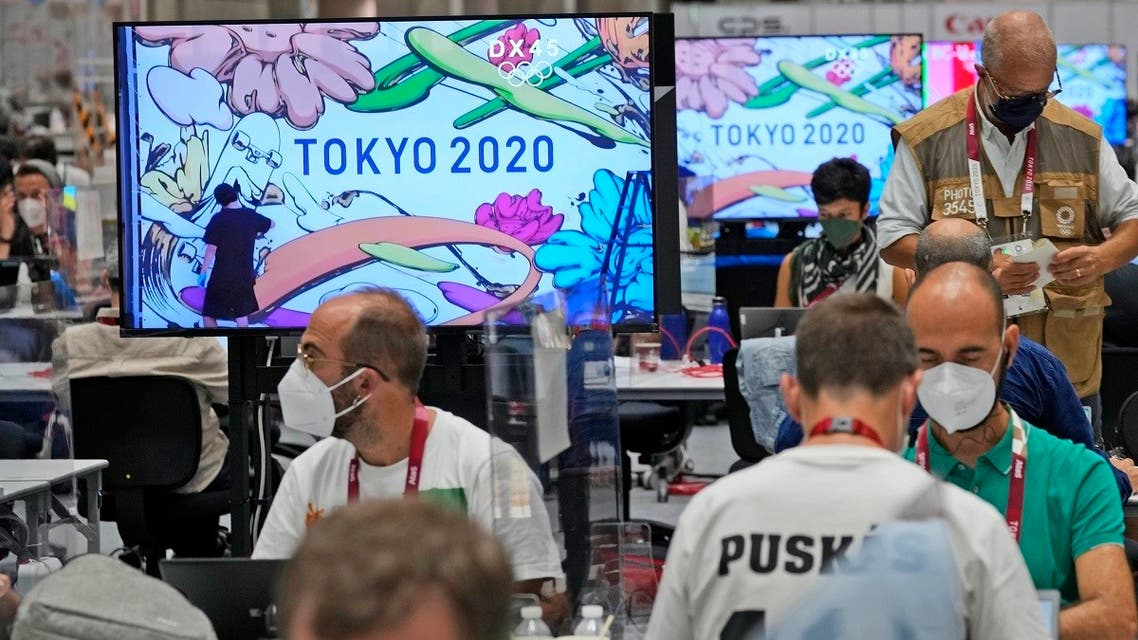 Journalists work as the making of a Tokyo 2020 mural is shown on television screens at the main press center of the 2020 Summer Olympics, Friday, July 23, 2021, in Tokyo, Japan. (AP)