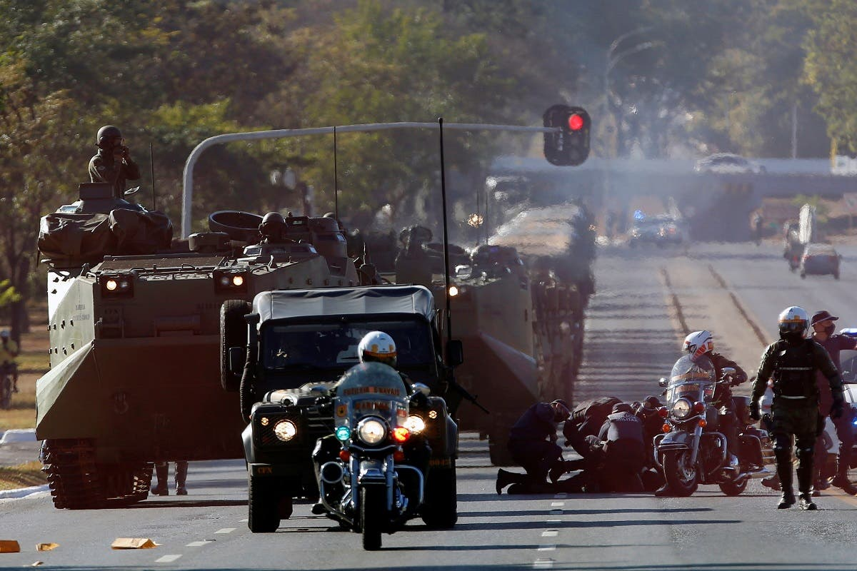 Police officers detain a protester who was trying to stop the Brazilian Navy tanks, next to the Planalto presidential palace during a military parade in Brasilia, Brazil, August 10, 2021. (Reuters/Adriano Machado)