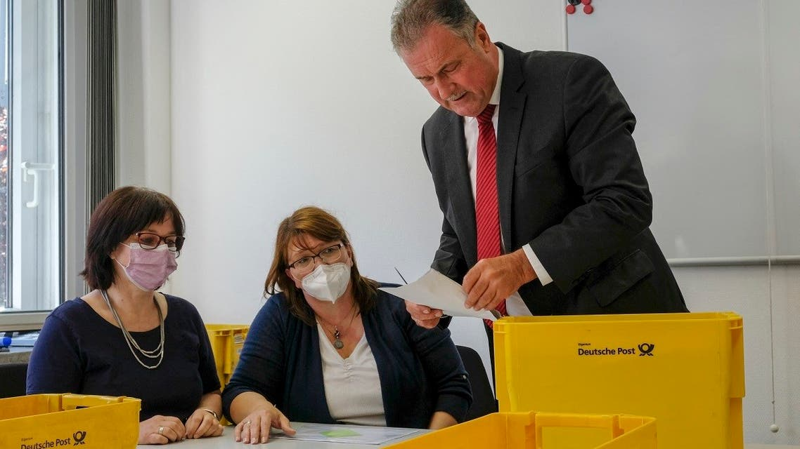 The chairman of the German train drivers' union GDL Claus Weselsky looks at an envelope of ballots before GDL members count the votes on possible strikes at Deutsche Bahn, on August 9, 2021 at the GDL headquarters in Frankfurt, western Germany. (AFP)