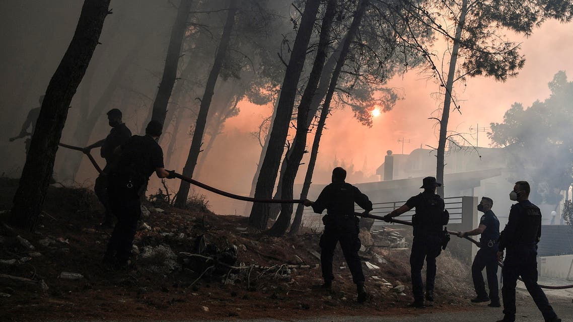 Police officers help firefighters to extinguish a fire in Thrakomakedones, near Mount Parnitha, north of Athens, on August 7, 2021. (File photo: AFP)