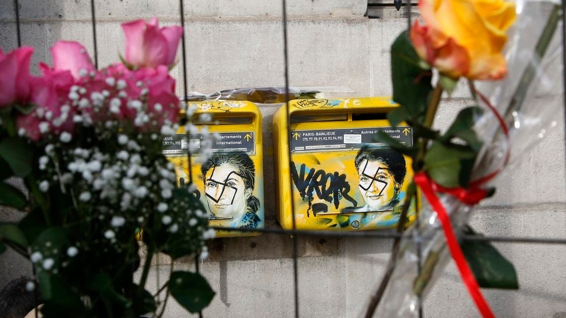 A file photo shows roses are placed next to vandalized mailboxes with swastikas covering the face of the late Holocaust survivor and renowned French politician, Simone Veil, before their renovation in Paris, February 12, 2019. (AP/Michel Euler)
