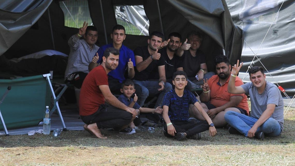 Migrants react to the camera as they sit by a tent in a camp near the border town of Kapciamiestis, Lithuania, on July 18, 2021. (Petras Malukas/AFP)