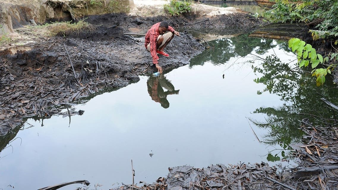 In this file photo taken on August 11, 2011 a man scoops spilled crude oil allegedly caused by Shell equipment failure floating at the bank of B-Dere waterways in Ogoniland, Rivers State. (Pius Utomi Ekpei/AFP)