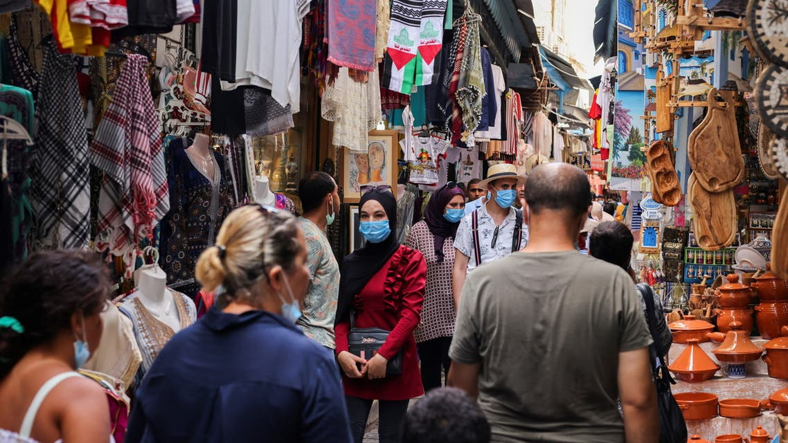 People wearing protective face masks walk past shops, amid the coronavirus disease (COVID-19) outbreak, in the Old City of Tunis, Tunisia, August 3, 2021. (Reuters)