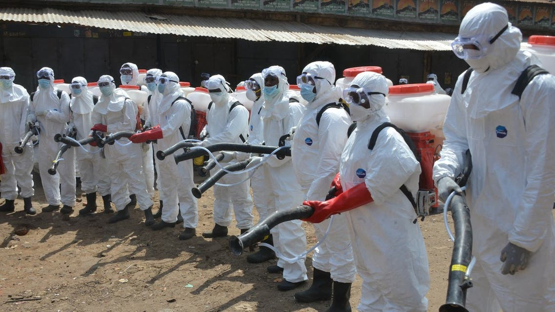 Workers dressed in full body gear prepares to disinfect shops and streets in Conakry, Guinea, on April 12, 2020 during a cleaning and disinfecting campaign as a preventive measure against the spread of the COVID-19 coronavirus. (File photo: AFP)
