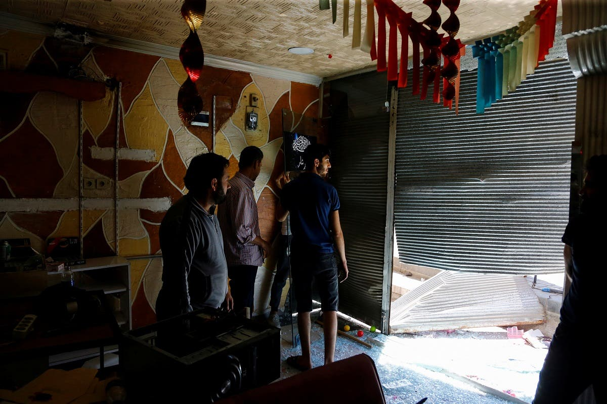 A Syrian shop owner and his friends check the damage in his shop after a crowd of Turks attacked shops and homes belonging to Syrians overnight, in the wake of a street fight that led to a Turkish youth being fatally stabbed, in Ankara, Turkey August 12, 2021. (Reuters)